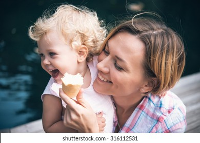 Mother and daughter eat ice-cream during a walk outdoors. Toned image