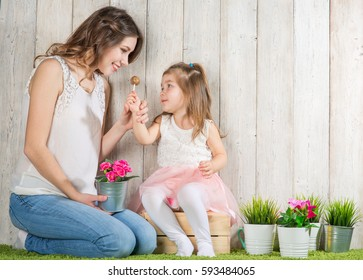 Mother and daughter eating candy lollipop