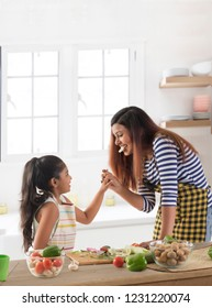 Mother and daughter eating cucumber in kitchen