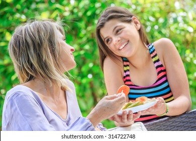 Mother and daughter eating fruits in outdoor