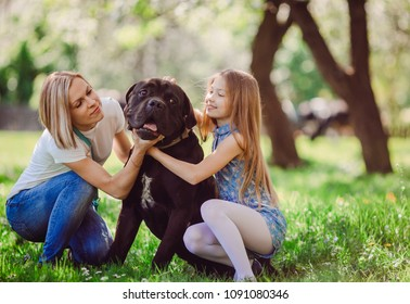 The mother and daughter  embracing a black  dog