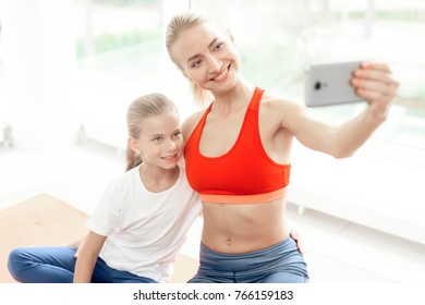 Mother and daughter are engaged in yoga in sportswear. They are in a bright room with panoramic windows. They are making selfie on the smartphone.