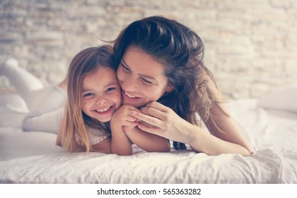 Mother and daughter enjoy in bed at home and looking at the camera.