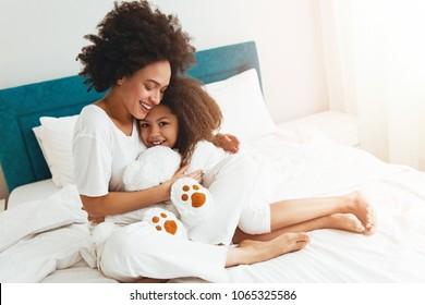 mãe e filha gozando no o cama feliz, sorrindo