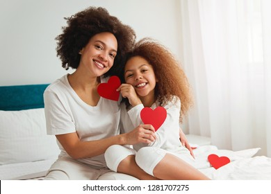 Mother and daughter enjoying on the bed, holding red hearts