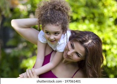 Mother and daughter are enjoying on grass at park