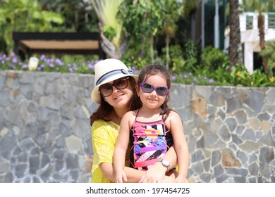 Mother and daughter enjoying the summer outdoors with fancy sunglasses.  Focus in the little girl.