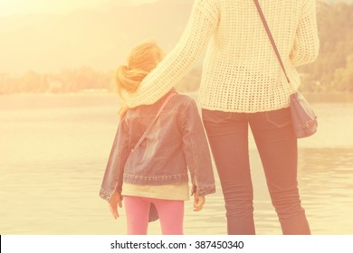 Mother and daughter enjoying sunset on a lake.