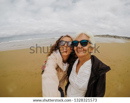 744613e3b6361 Mother and daughter enjoying their holidays together, taking photos on the  beach on a cloudy summer day in north of Spain. Close relationship.  Lifestyle.