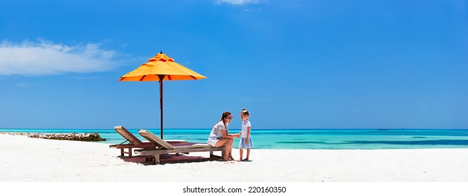 Mother and daughter enjoying time at tropical beach during luxury tropical vacation