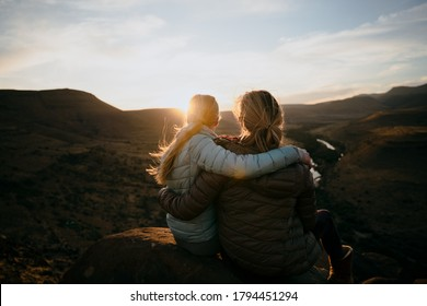 Mother and Daughter enjoying the view after a mountain hike during sunset