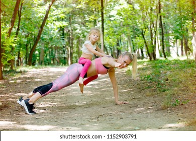 Mother and daughter exercise together in park