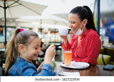 Mother and daughter with face mask indoors in cafe in shopping center, coronavirus concept.
