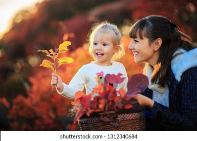 Mother and daughter with fallen leaves in autumn park. Little girl and her mom playing in the garden.