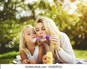 Mother and daughter family time, blowing bubbles