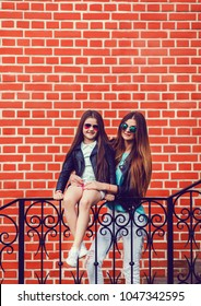 mother and daughter in fashion clothes on a brick wall background