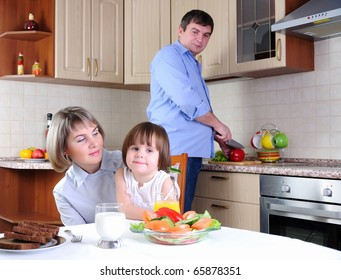 Mother, daughter and father has breakfast in the kitchen. father prepares a salad. Mom and daughter sit at the table.