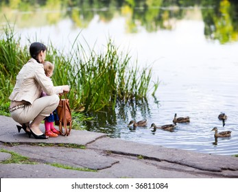 Mother and daughter feeding ducks - shallow DOF, focus on people
