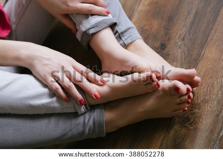 Mother and daughter feet with red polished toes on the wood background