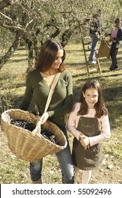 Mother and daughter in a field during a olives harvest