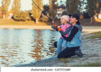 mother and daughter are fishing on the lake. Family activities