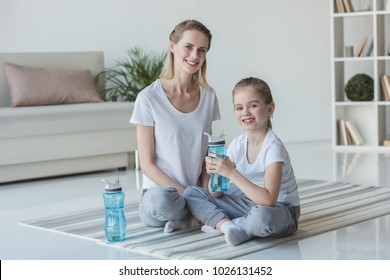 mother and daughter with fitness water bottles sitting on yoga mats
