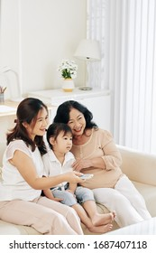 Mother, daughter and granddaughter spending time together and watching tv at home