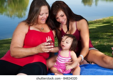 A mother, daughter and grandmother having a picnic near a lake
