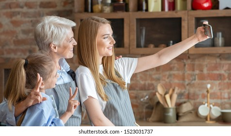 Mother, daughter and grandmother taking selfie at kitchen, side view, panorama with empty space