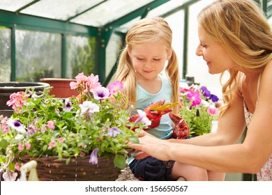 Mother And Daughter Growing Plants In Greenhouse