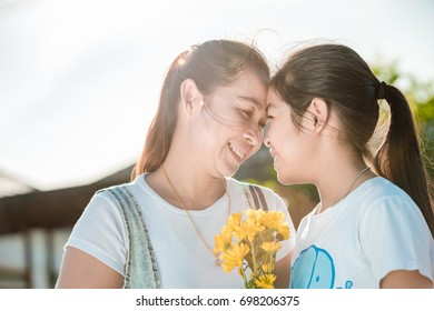Mother and daughter handed flowers to smiling happily together on Mother's Day.