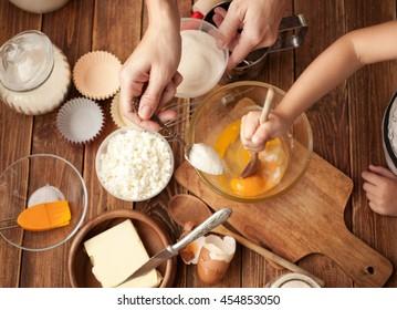 Mutter und Tochter bereiten den Teig auf dem Tisch vor. Zutaten und Vorrichtungen für den Tasse-Kuchen auf Holzhintergrund. Gebäck. Lebensmittelkonzept. Mehl, Eier, Butter, Mehl für Gebäck mischen. Draufsicht