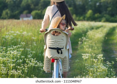 Mother and daughter have bike ride on nature. Summertime activity
