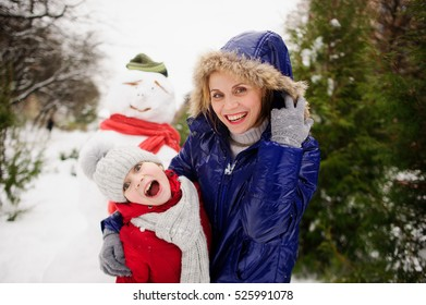 Mother and the daughter have built a snowman and rejoice. Snowman in a hat and a scarf stands behind their backs. They make funny faces. All ground in park is completely covered with fluffy snow.