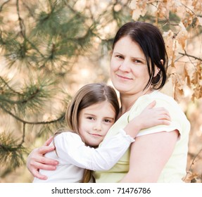 Mother and daughter have fun - beautiful forest in background