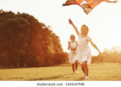 Mother and daughter have fun with kite in the field. Beautiful nature.