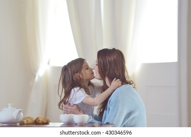 mother and daughter are having breakfast