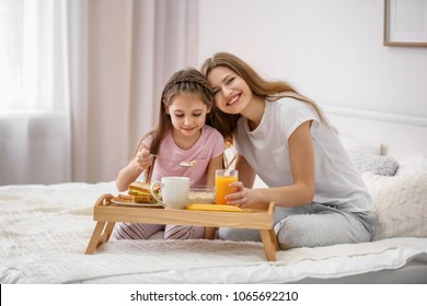 Mother with daughter having breakfast in bed