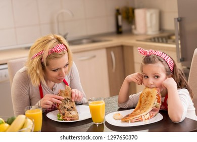 Mother and daughter having breakfast in the kitchen; daughter refuses to eat. Focus on the mother