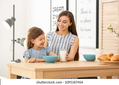 Mother and daughter having breakfast with milk at table