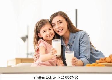 Mẹ và con gái ăn sáng với sữa tại bàn