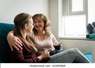 Mother with daughter having casual talk in living room
