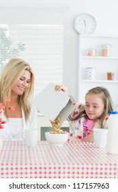 Mother and daughter having cereal at breakfast