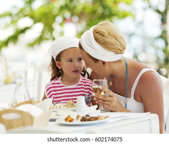 Mother and daughter having dinner in a outdoor restaurant