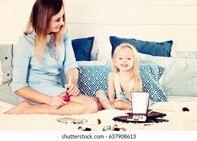 Mother and Daughter Having Fun. Mother and Daughter doing Makeup and Sitting on the Bed in the Bedroom. Happy Loving Family