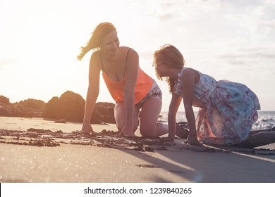 Mother and daughter having fun drawing with sand  at sunset on tropical beach - Happy mom playing with her kid in vacation - Love, happiness and family lifestyle concept