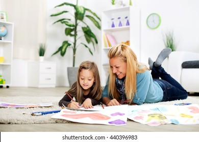 Mother and daughter are having fun drawing and lying on the floor