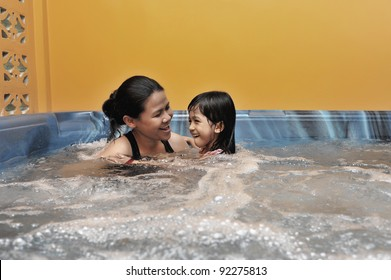 Mother and daughter having fun during Jacuzzi session.