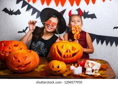 Mother and daughter having fun at home. Happy family preparing for Halloween. People wearing carnival costumes.