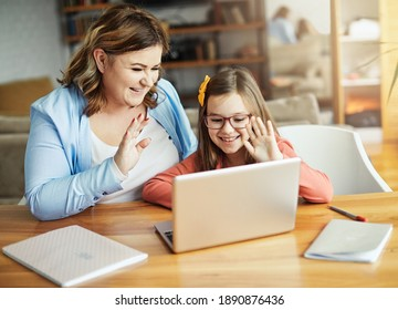 Mother and daughter Having fun with laptop at home having a video call during online education class